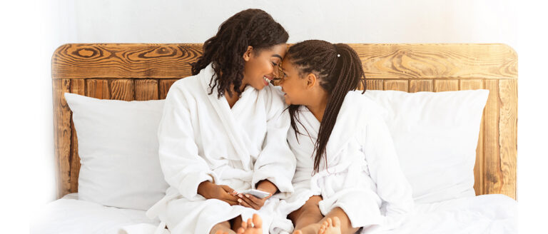 Daughter kissing her mother at the white bed